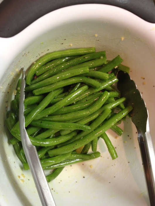 Coating green beans in olive oil and garlic